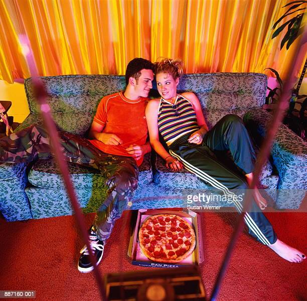 teenage couple (15-17) sitting on couch, pizza on floor, elevated - petit ami photos et images de collection