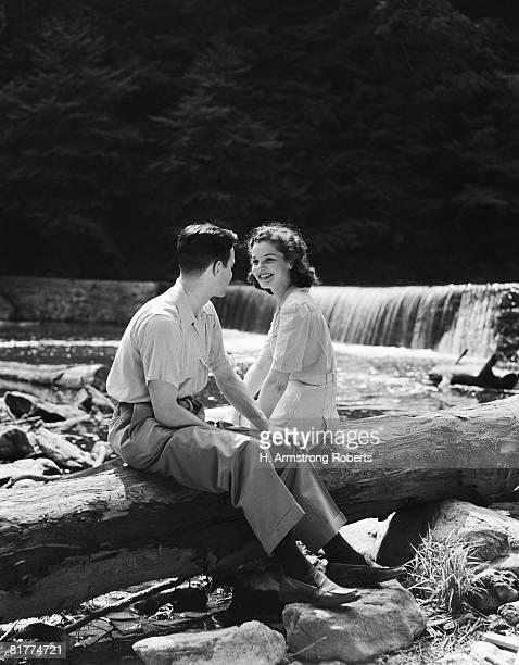 Teenage couple sitting on fallen log by side of creek, talking.