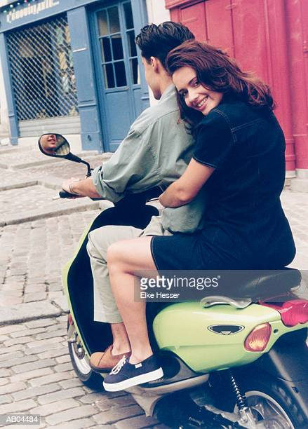 Teenage couple sitting on motor scooter, rear view