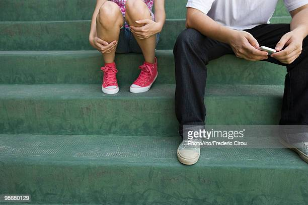 Teenage couple sitting together on steps