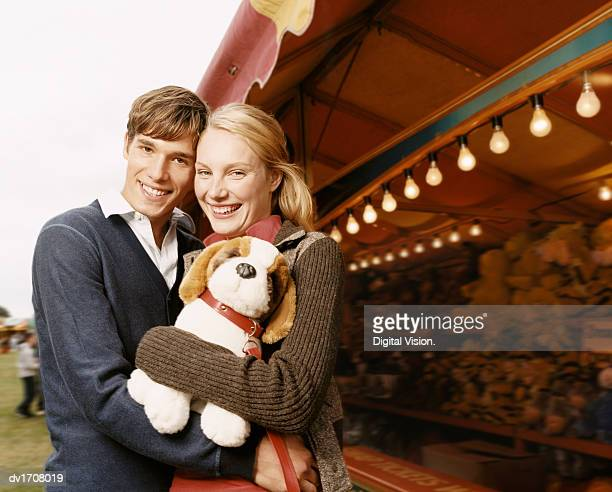teenage couple stand by a fairground stall, smiling, the girl holding a cuddly toy - teen awards stock-fotos und bilder