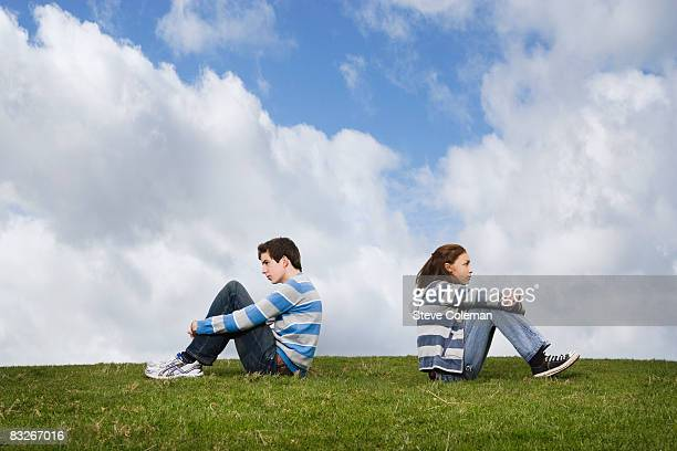 teenage couple turned away from one another in field - girl fight stock photos and pictures