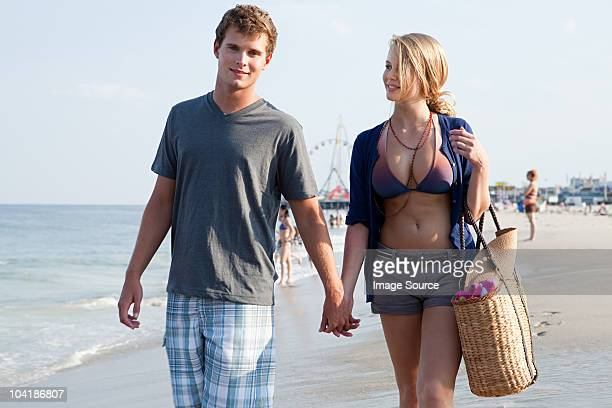Teenager paar gehen hand in hand am Strand