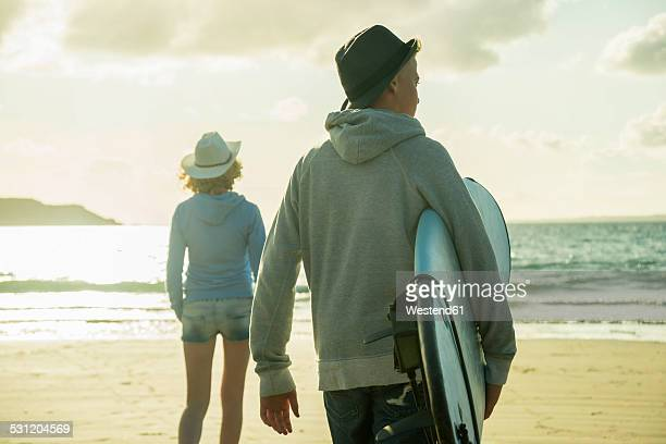 Teenage couple walking on the beach at evening twilight