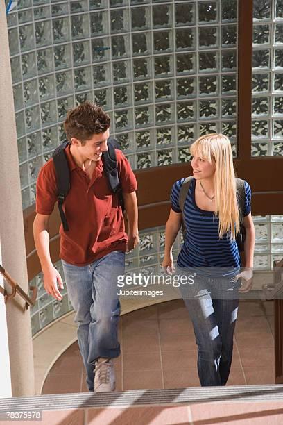 Teenage couple walking up stairs