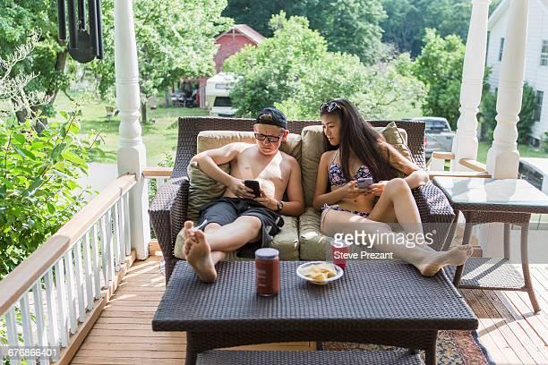 Teenage couple wearing bikini and swim shorts reclining on patio sofa sharing smartphone reading