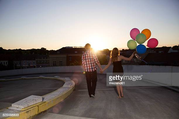 Teenage couple with balloons on parking ramp