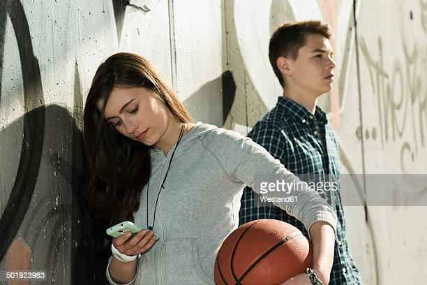 Teenage couple with basket ball and smartphone