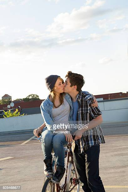 Teenage couple with bicycle kissing outdoors
