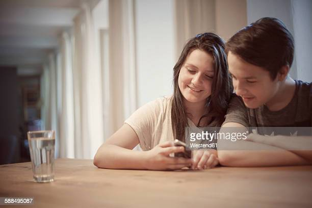 Teenage couple with smartphone at home