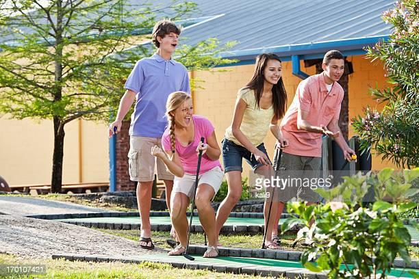 Teenage couples playing miniature golf