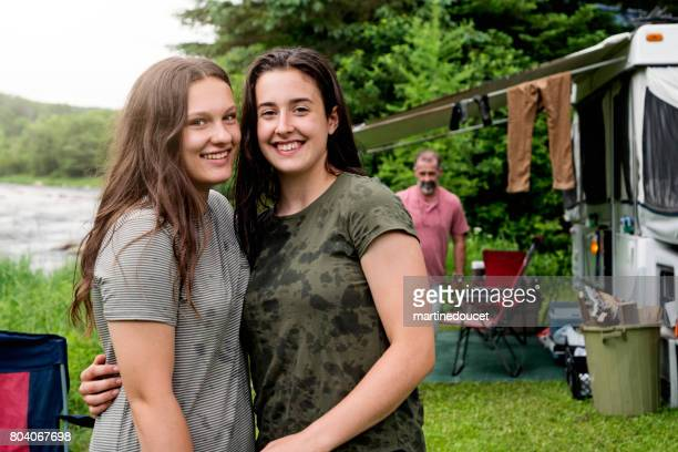Teenage cousins hugging in camping outdoors in summer.
