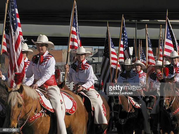 CONTENT] Teenage cowgirls on horses dressed in western attire and holding US flags ride with a spirit of American patriotism through the streets of...