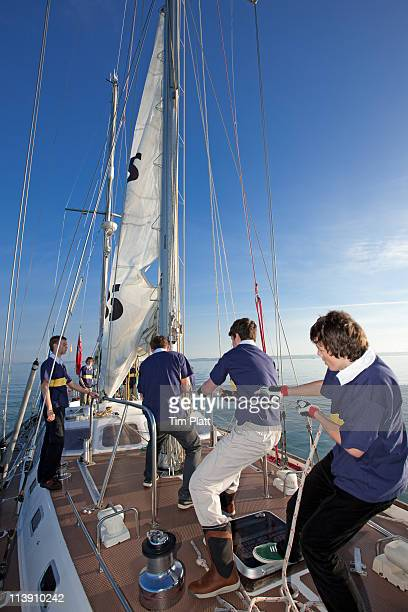 teenage crew raising the sail on a yacht. - sailing team stock pictures, royalty-free photos & images