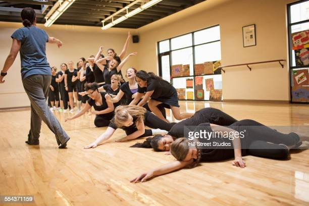 Teenage dancers rehearsing with teacher in studio