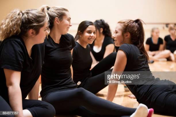 Teenage dancers sitting on studio floor