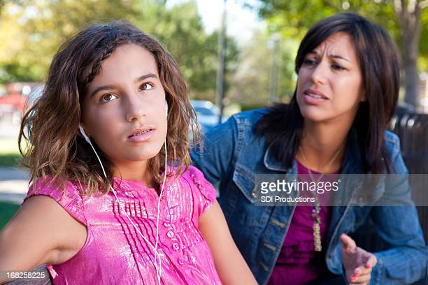 Teenage daughter looking away from her concerned mother