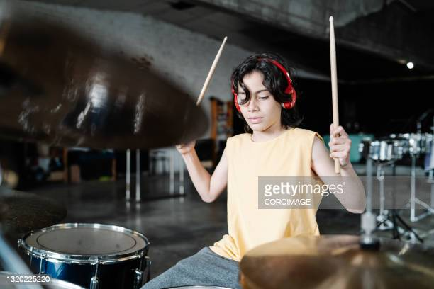 teenage drummer in tank top playing the drums looking away - early rock & roll stock pictures, royalty-free photos & images