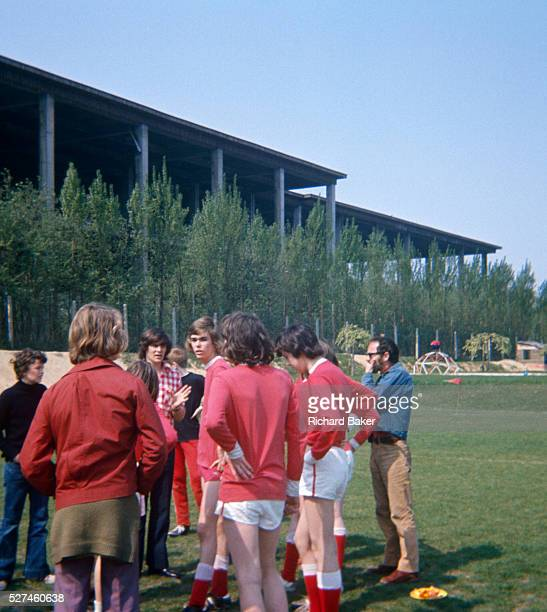 Teenage epat football players listen to their PE teacher during a halftime pep talk during their match at the British School of Brussels in 1975 The...