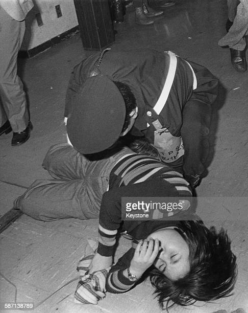 Teenage fan is helped by a policeman, having fainted during a Bay City Rollers concert at the Budokan in Tokyo, Japan, December 1976.