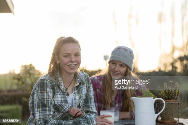 Teenage farm girls at outdoors table with milk.