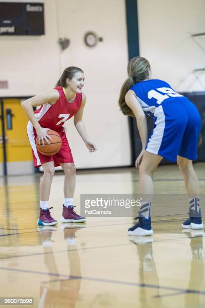 teenage female basketball player dribbles at the top of the key - charging sports stock pictures, royalty-free photos & images