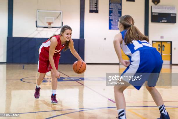 teenage female basketball player goes one-on-one against another girl - dribbling sports stock pictures, royalty-free photos & images