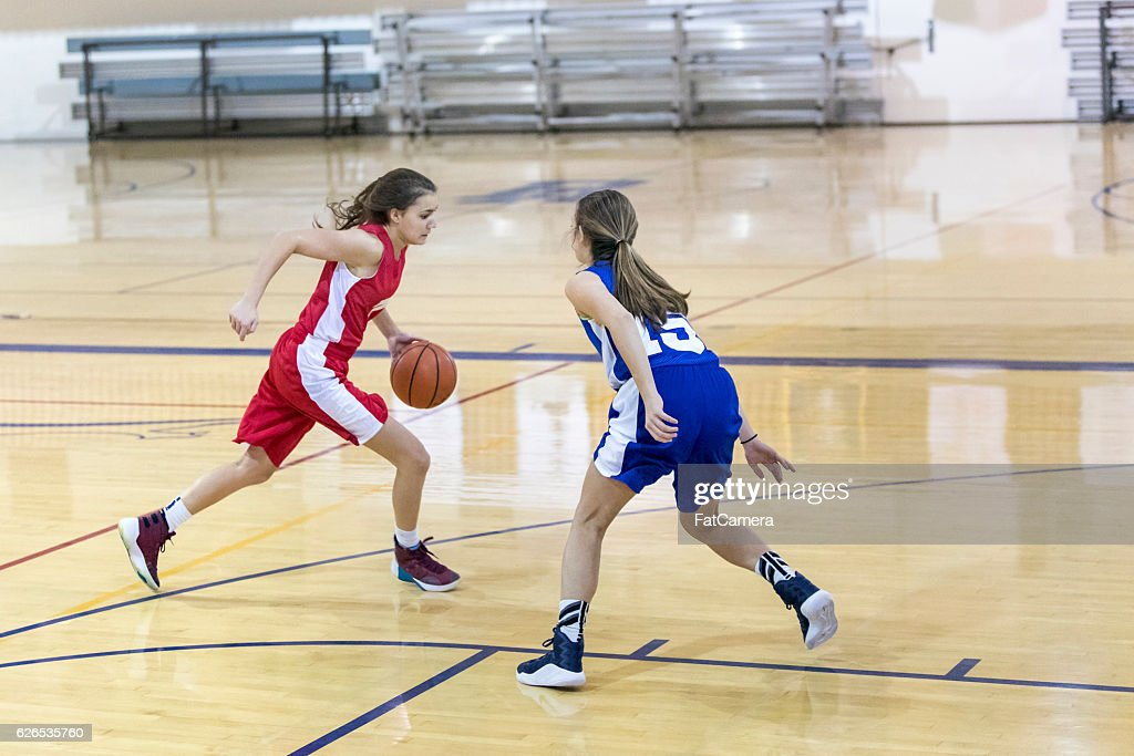Teenage female basketball player one on one against another girl : Stock Photo
