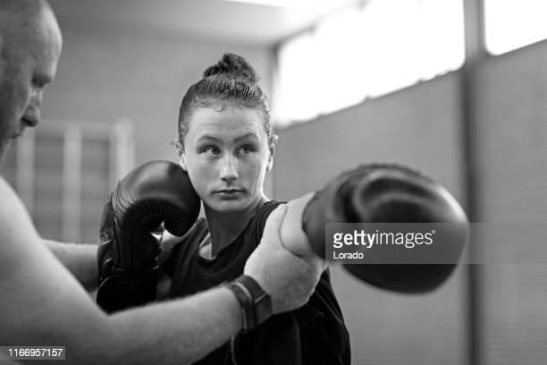 teenage female fighter meisje en trainer in een openbare sportschool - vechtsport stockfoto's en -beelden