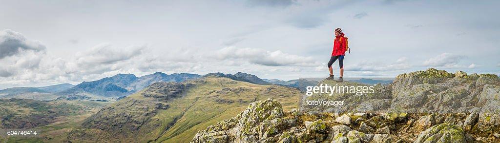 Teenage female hiker on rocky mountain summit overlooking peak panorama : Stock Photo