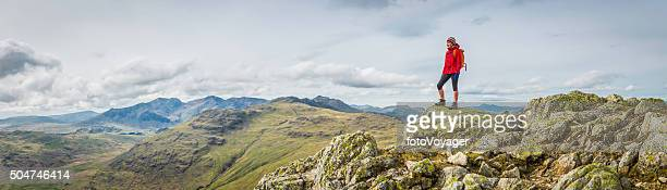 teenage female hiker on rocky mountain summit overlooking peak panorama - lake district stockfoto's en -beelden