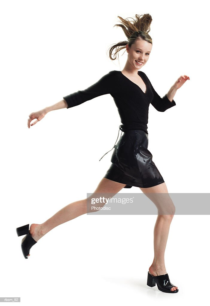 teenage female in a black skirt and blouse jumps and steps forward in long strides turns and smiles : Foto de stock