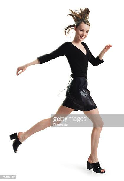 teenage female in a black skirt and blouse jumps and steps forward in long strides turns and smiles