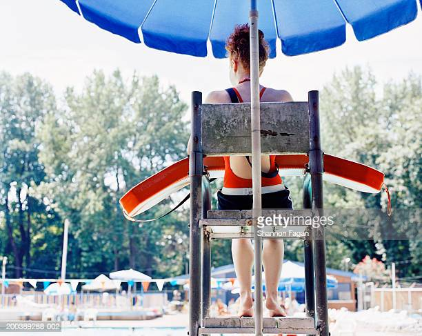 teenage female lifeguard (14-16) watching pool, rear view - lifeguard stock pictures, royalty-free photos & images