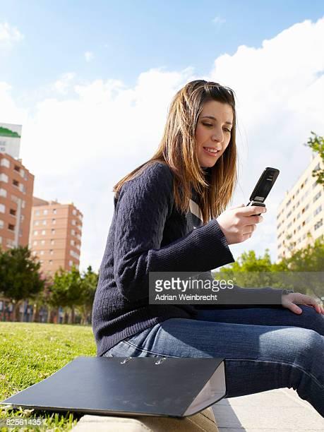Teenage female on mobile phone in park