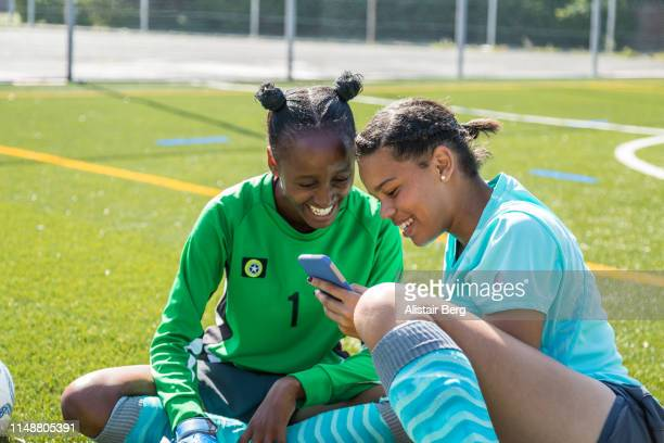Teenage female soccer players looking at phone