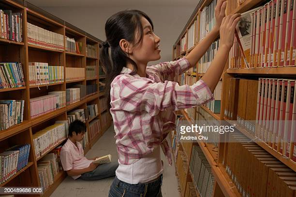 Teenage female student (12-14) taking book from shelf, side view