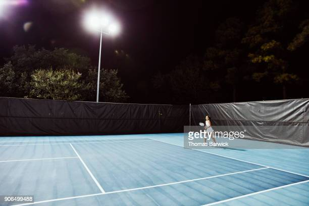 Teenage female tennis player practicing on outdoor court at night
