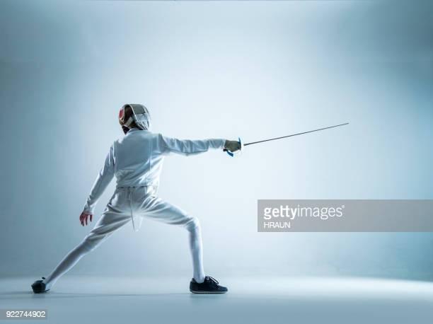 adolescente esgrimista de pé em posição de lunge - esgrima esporte de combate - fotografias e filmes do acervo