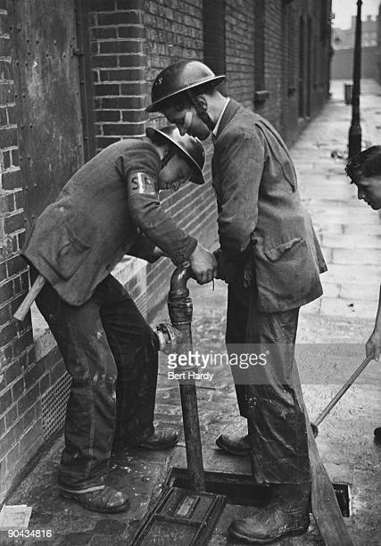 Teenage firefighters connect a hose to a hydrant London April 1941 They are members of the 'Dead End Kids' a gang of teenage boys from the East End...