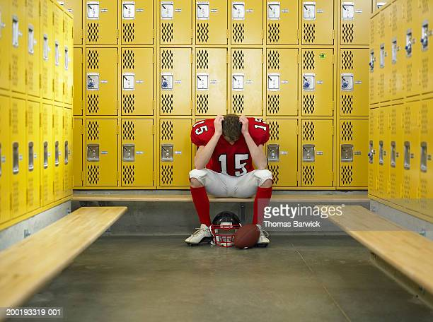 teenage football player (15-17) hanging head in locker room - american football uniform stock pictures, royalty-free photos & images