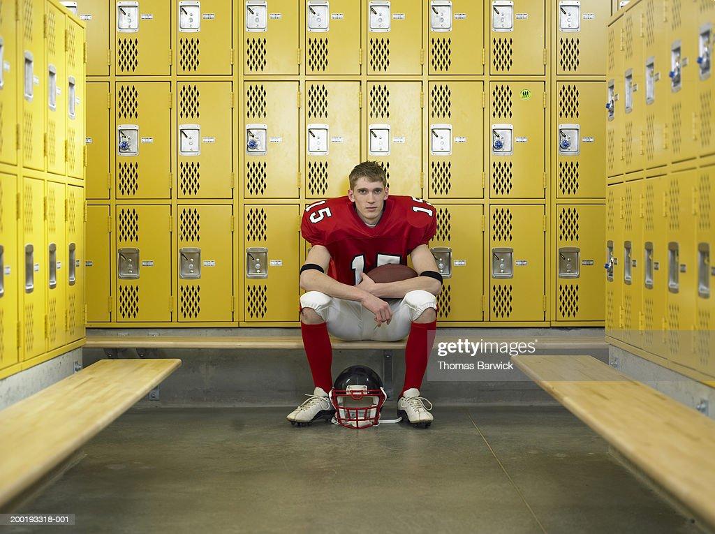 Teenage football player (15-17), sitting in locker room, portrait : Stock Photo