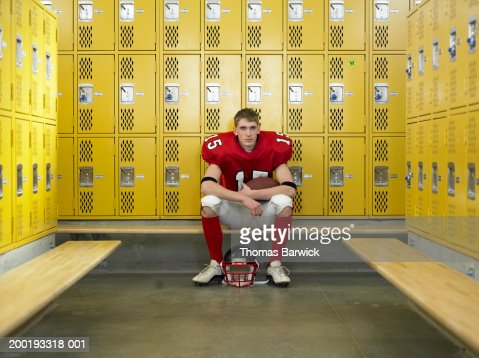 Teenage football player (15-17), sitting in locker room, portrait