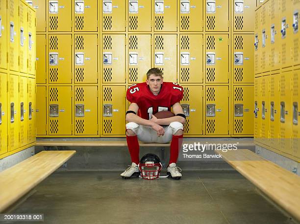 teenage football player (15-17), sitting in locker room, portrait - high school football stock pictures, royalty-free photos & images