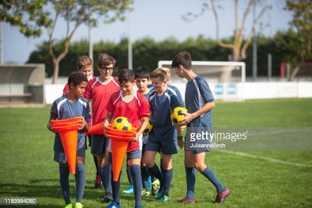 teenage footballers carrying cones and balls for practice - sports training camp stock pictures, royalty-free photos & images