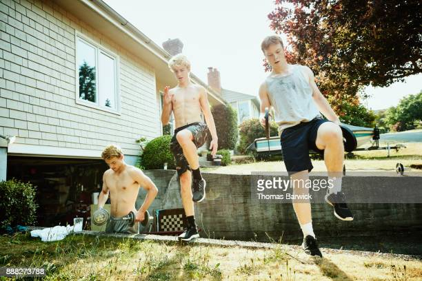 Teenage friends doing plyometric exercises on driveway wall in front of home on summer afternoon