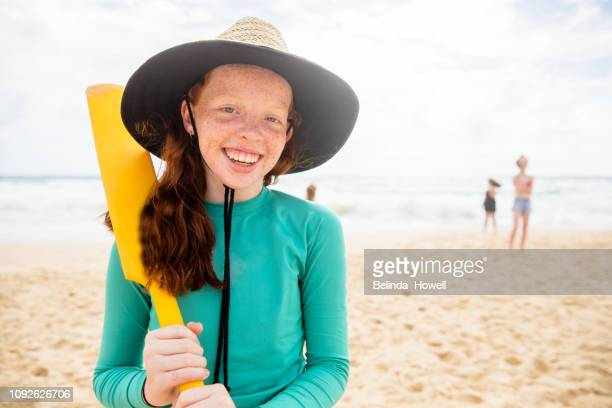 teenage friends enjoy each others company whilst playing, running and talking on an australian beach - beach cricket stock pictures, royalty-free photos & images