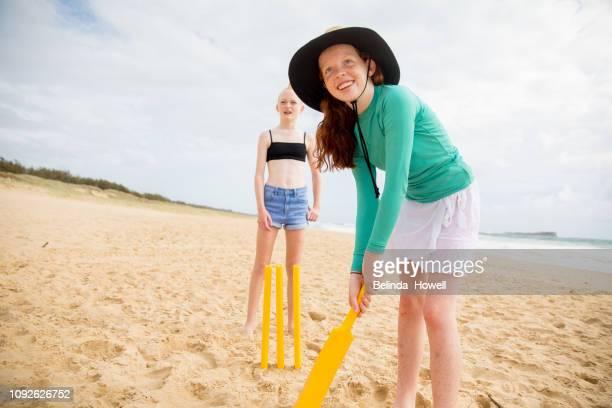 teenage friends enjoy each others company whilst playing, running and talking on an australian beach - cricket spieler stock-fotos und bilder