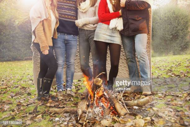 teenage friends enjoying campfire in autumn park - blanket stock pictures, royalty-free photos & images