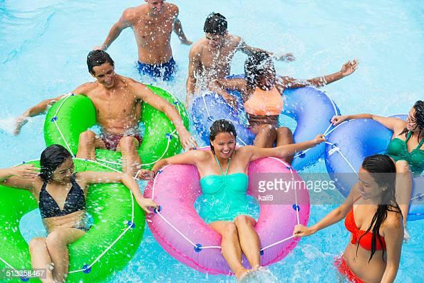 Teenage friends floating on innertubes